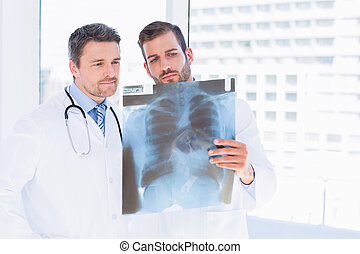 Male doctors examining x-ray in medical office - Two male...