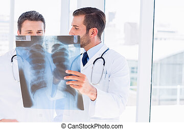Two male doctors examining x-ray in a bright medical office