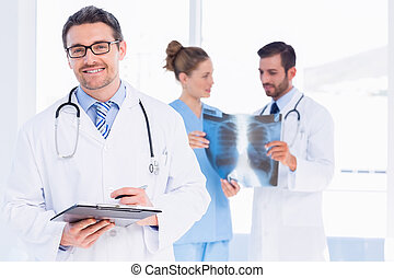 Doctor holding reports with colleagues examining x-ray -...