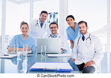 Happy medical team using laptop together - Portrait of a...