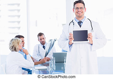 Doctor holding digital tablet with colleagues in meeting at...
