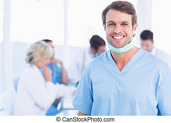 Smiling male surgeon with colleagues in meeting - Portrait...