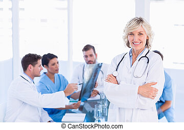Smiling female doctor with colleagues in meeting - Portrait...