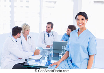 Smiling female surgeon with colleagues in meeting