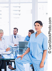 Serious female surgeon with colleagues in meeting - Portrait...