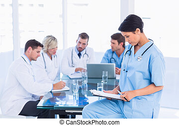 Female surgeon looking at reports with colleagues in meeting...