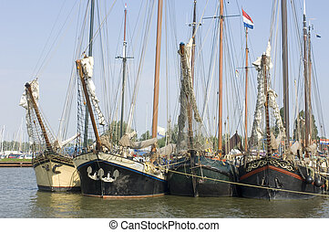 Bows in a row - A row of old sailing vessels, neatly...