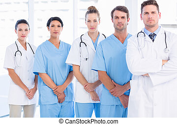 Portrait of serious confident group of doctors standing at...