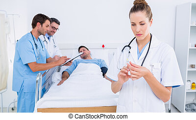 Serious female doctor holding a syringe with colleagues and patient in background at hospital