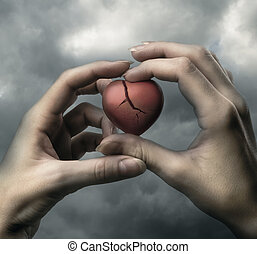 Broken red heart in hands on stormy sky