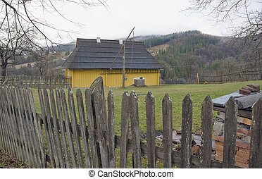 Yellow house in the country. - House with well behind wooden...