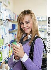 pharmacy - Portrait of blonde woman choosing shampoo in...