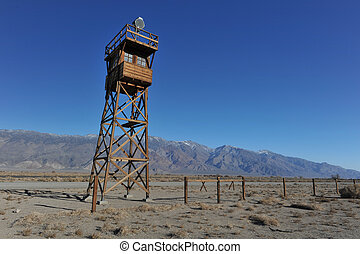 Wooden guard tower in desert by mountains - Guard tower with...