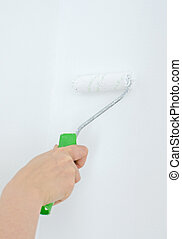Female hand holding roller with paint on the wall.