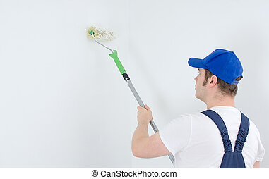 Painter in uniform paints the wall Space for your text