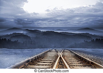 Train tracks leading to misty mountains