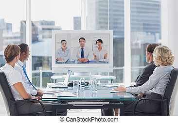 Business team having video conference with another business...