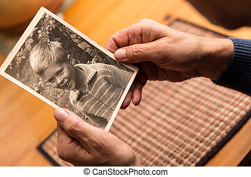 close up from a man with old photo - close up from a male...