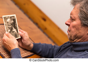 portrait of a man with old photo - senior adult watching a...