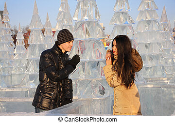 Young couple stand near ice spruce in ice forest and look at each other at sunny winter day.