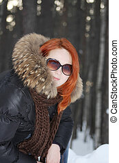 Happy girl in clothes with fur and sunglasses smiles in...
