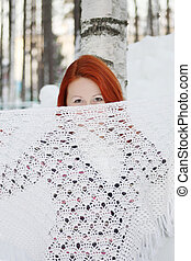 Pretty girl hides her face behind shawl near tree and huge...