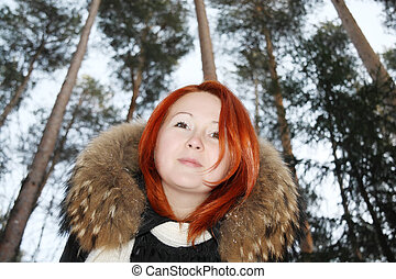 Happy redhead girl looks at camera in pine forest at winter.