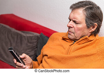 senior citizen on a couch with phone