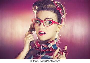 Beauty young pin-up woman with retro telephone
