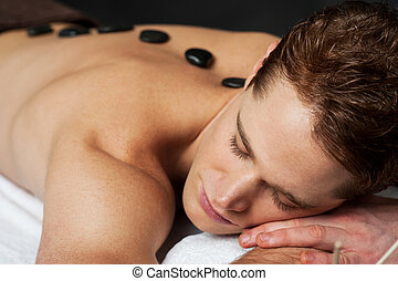 Man having massage at spa - Young man getting a hot stone...