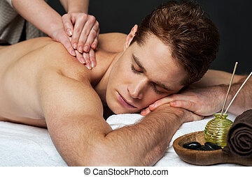 Man getting relaxing massage in spa - A good looking man...