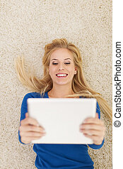 Smiling beautiful woman lying on carpet and using digital tablet