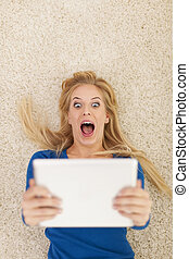 Surprise young woman lying on carpet and using digital tablet