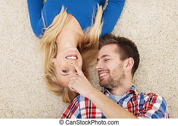 Lovely couple flirting on carpet