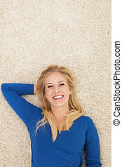 Beautiful smiling woman lying down on carpet