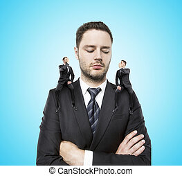 small adviser - on shoulders of a businessman siting two...