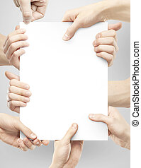 many hands holding paper - many hands holding poster on gray...