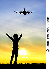 child looking the airplane at sunset