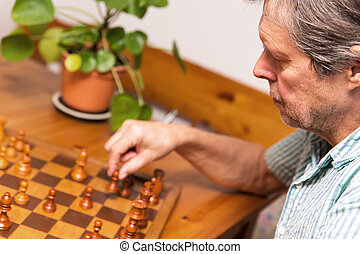 closeup, man is playing chess - closeup, senior adult is...