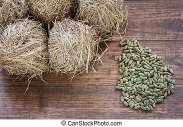 Rodent food and hay on grunge wooden background.