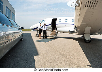 Stewardess And Pilot Standing Neat Limousine And Private Jet...