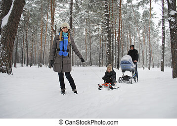 Family on a walk in a winter snow-covered forest.