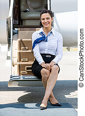 Stewardess Sitting On Ladder Of Private Jet - Full length...