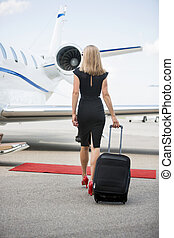 Woman With Luggage Walking Towards Private Jet - Rear view...