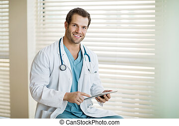 Happy Cancer Specialist Holding Digital Tablet At Clinic -...