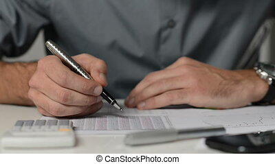 Businessman analyzes graphs - Doing calculations at the...