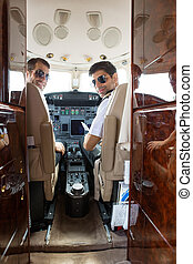Confident Pilot And Copilot In Cockpit - Portrait of...
