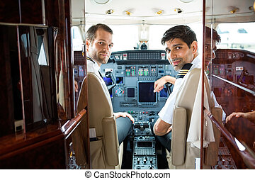 Pilots In Corporate Plane Cockpit - Portrait of confident...