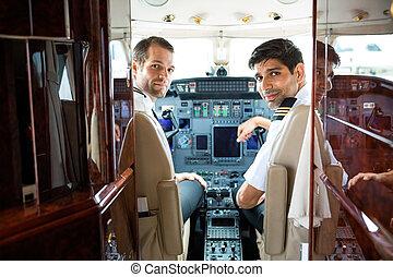 Pilots In Corporate Plane Cockpit - Portrait of confident...