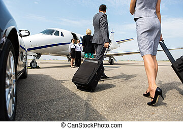 Business Partners Walking Towards Private Jet - Business...